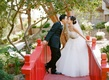 bride and groom kiss on red bridge