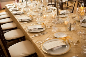 Tan table linens with gold-rimmed chargers and glassware