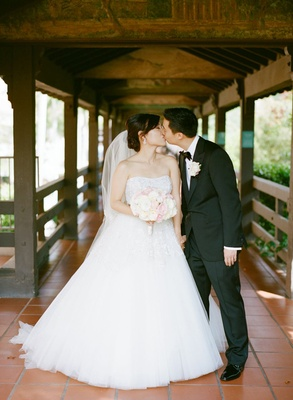 bride and groom kiss on tiled path covered with wooden roof