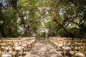 Wood chairs under canopy of trees outdoor wedding ceremony natural theme camp theme rustic wedding