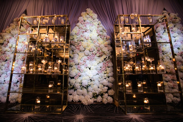 Wedding reception with a modern mirrored metal stands, candles, floral panels of white hydrangeas