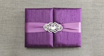 Violet gatefold wedding invitation box with light purple ribbon, crystal brooch