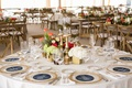 White round table with gold rim charger plate and gold box low centerpieces
