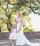 Bride in sheer cutout wedding dress with flower girl in cute dress layer ruffle skirt halo headband