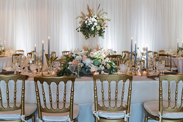 wedding reception gold chair white cushion high low centerpiece taper candles drapery