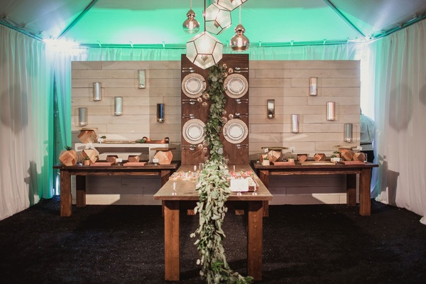 wedding reception food station with table that appears to climb wall
