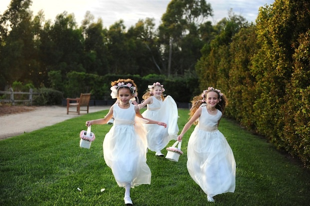 Three flower girls running in white dresses at wedding