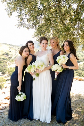 bride in reem acra wedding dress with beaded cap sleeves, bridesmaids in mismatched navy dresses