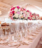 wedding reception tent venue blush linen on long head table ghost chair tall pink white centerpiece