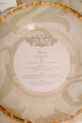 wedding reception place setting gold rim charger plate round menu card gold blue design motif