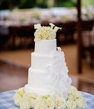 White wedding cake with large sugar flower topped with white calla lilies and ivory hydrangeas