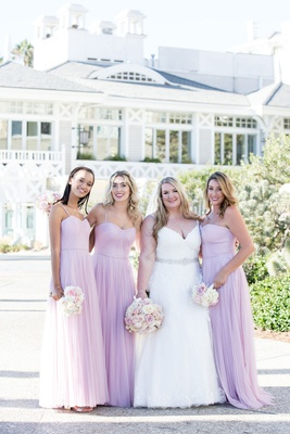 bride in v neck ball gown with silver sash and bridesmaids in pink lavender purple gowns blush