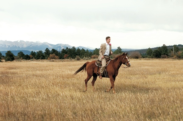 Groom riding brown horse at Colorado ranch wedding venue