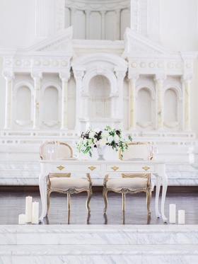 White sweetheart table, vintage chairs, white flowers, greenery, purple leaves at Vibiana