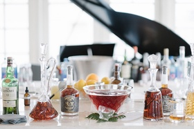 Whisky and bourbon bar at wedding reception in front of piano glass decanters and botles