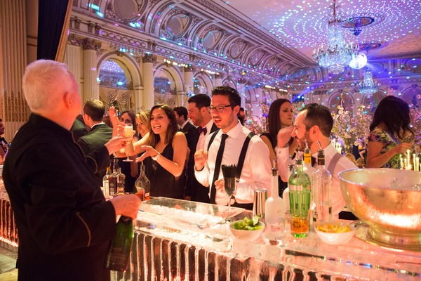 guests order drinks at ice bar at wedding reception in the plaza