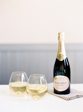 champagne bottle with two stemless glasses with flowers floating