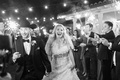 Black and white photo of bride in Oscar de la Renta dress and groom cowboy hat during sparkler exit