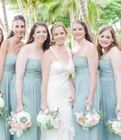 bridesmaids in sage dresses with bride in white bridal gown and pastel bouquets