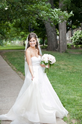 a beautiful bride shows off her delicate a-line wedding gown outside the church