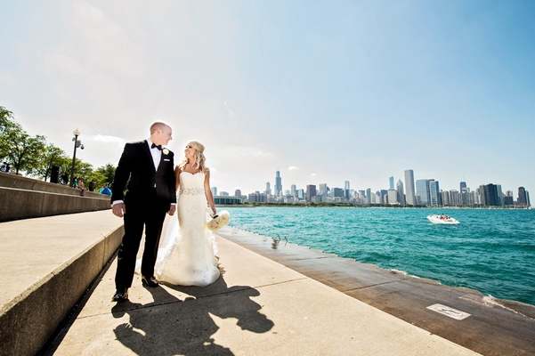 bride in vera wang, groom in vera wang, newlyweds walk alongside lake michigan
