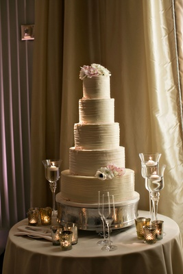 Wedding cake five layer with fresh flowers on top tier and bottom tier floating candles on table