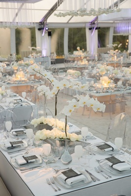 white orchid and ivory rose centerpieces in silver vases white goblets tent wedding purple lighting
