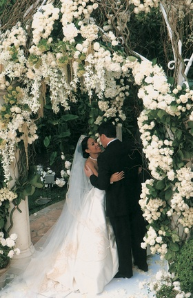 Bride and groom under white flower ceremony structure