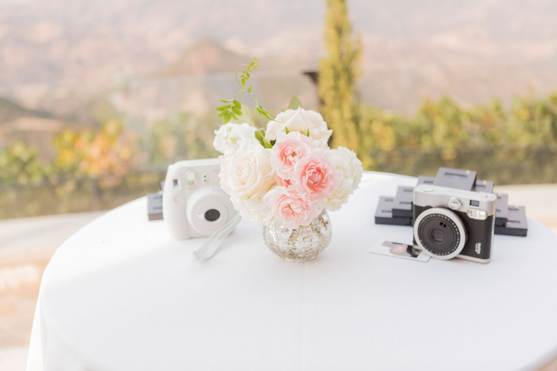 Wedding reception white linen cocktail table with pink and white flower bud vase instax cameras