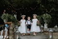 two cute flower girls white dresses moss baskets ring bearer in suspenders high socks bow tie