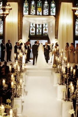 White aisle lined with silver candelabra