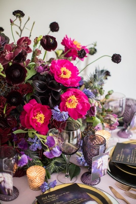 Dark orchids, calla lilies, ranunculus, purple pink flowers purple glassware unicorn place card