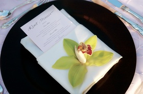Brown charger plate with white napkin and flower