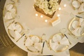 Aerial view of place settings with gold rimmed chargers, gold napkin rings and flatware