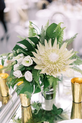 low wedding centerpiece king protea white flower monstera leaf fern gold candle votives tropical