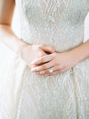 bride in sparkling sequin lazaro wedding dress with double halo engagement ring on finger wedding