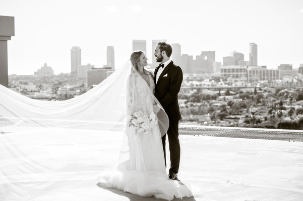 black and white photo of bride and groom on rooftop of four seasons hotel los angeles city view la