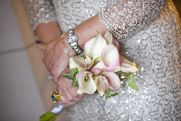 Mother of the bride at wedding in a long-sleeve sequined dress holds white calla lily bouquet