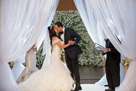 Bride in off shoulder wedding dress kisses groom at wedding under draped chuppah white flowers