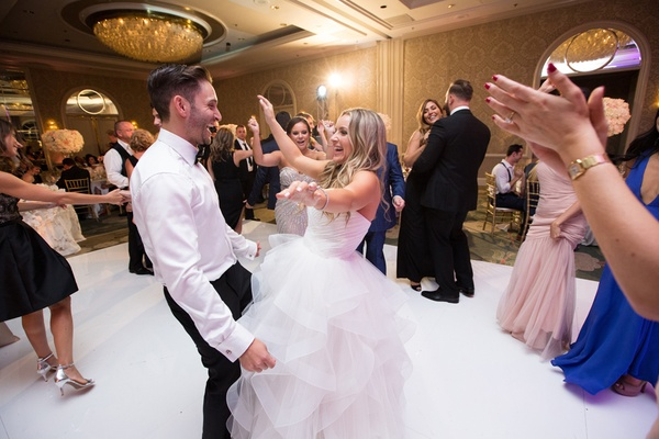 bride in reem acra ball gown dances with husband and guests at wedding reception