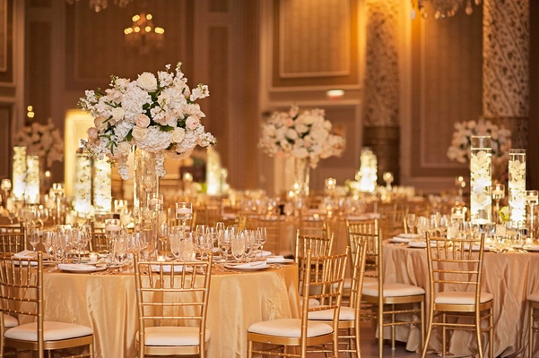 gold tablescapes with gold table linens chairs and charger plates tall floral arrangements