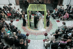 Ceremony in the round with chuppah decorated with green dendobrium orchids
