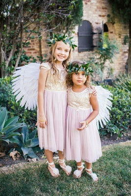 Two flower girls in dresses with short sleeves, sparkly golden bodices, blush tulle skirts