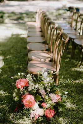 outdoor wedding ceremony wood vineyard x back chairs grass flower arrangement pink peony flowers