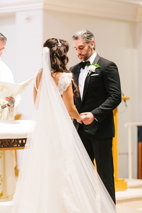Bride with long hair and veil pretty straps holding groom hand during ceremony bow tie pastor cantor