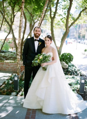 Bride in strapless a line ball gown Peter Langner wedding dress groom in tuxedo bow tie green flower