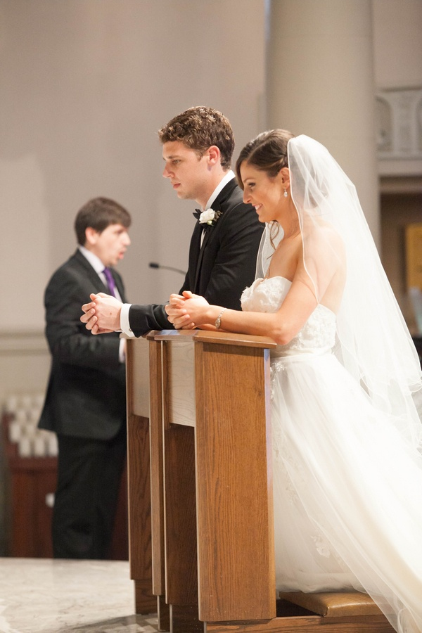 bride in Winnie Couture wedding dress and groom in prayer at Catholic ceremony