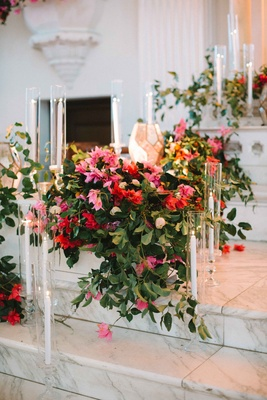 cascading bold florals ceremony altar marble steps glass votives