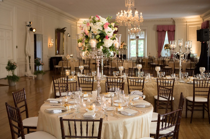 Ivory reception tables with candlestick centerpieces and chandeliers
