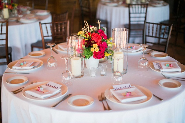 a simple white tablescape on round table with small floral arrangement red yellow pink flowers